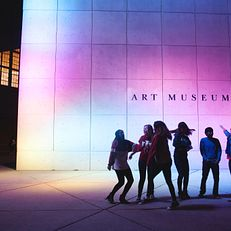 branding photo shoot - students outside art museum dancing in the light from the totem