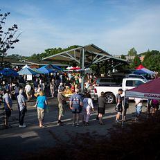 People wait in line for sweet corn during the Bloomington Farmer's Market on Saturday, July 25, 2015, in downtown Bloomington.