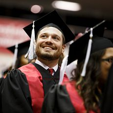 A graduate smiles before the start of the Indiana University Northwest Commencement at the Genesis Convention Center on Thursday, May 9, 2019.