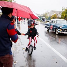 A unicyclist high fives parade goers along Woodlawn Avenue during the IU Bloomington Homecoming Parade on Friday, Oct. 11, 2019.
