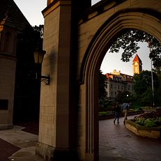 The Frances Morgan Swain Student Building clocktower is pictured through the Sample Gates at Indiana University Bloomington on a summer evening on Friday, June 21, 2019.