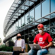 IUPUI students wearing a mask sit outside the ICTC building. Physical-distancing guidelines were followed while capturing this photo. Photo taken Thursday, June 25, 2020.