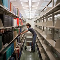 Becca Niles, a Stacks Unit Manager at the Herman B Wells Library, moves books from a shelf in the stacks on Tuesday, March 10, 2015, in the East tower of the library. Niles had the most individual competitions (30) in Healthy IU's Climb IU challenge.