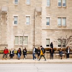Students wait for the bus outside of Hodge Hall at the Kelley School of Business during the first day of spring semester classes at Indiana University Bloomington on Monday, Jan. 13, 2020.