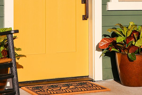 Porch with yellow door and welcome mat