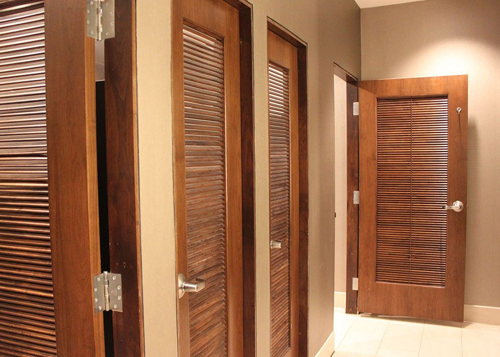 Full louver Masonite Algoma interior slotted restroom doors in a hotel bathroom