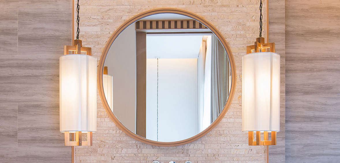 Circular mirror reflects pentameter lamps and Pretty + Calm color palette