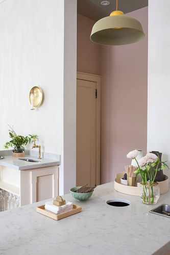 Pretty + Calm kitchen with white walls, marble counter, fresh flowers and pink accents