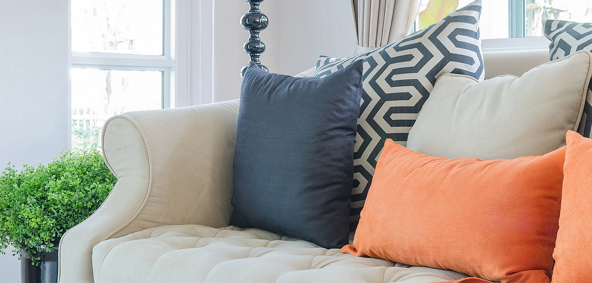 Orange, white and blue throw pillows in Mediterranean Escape living room