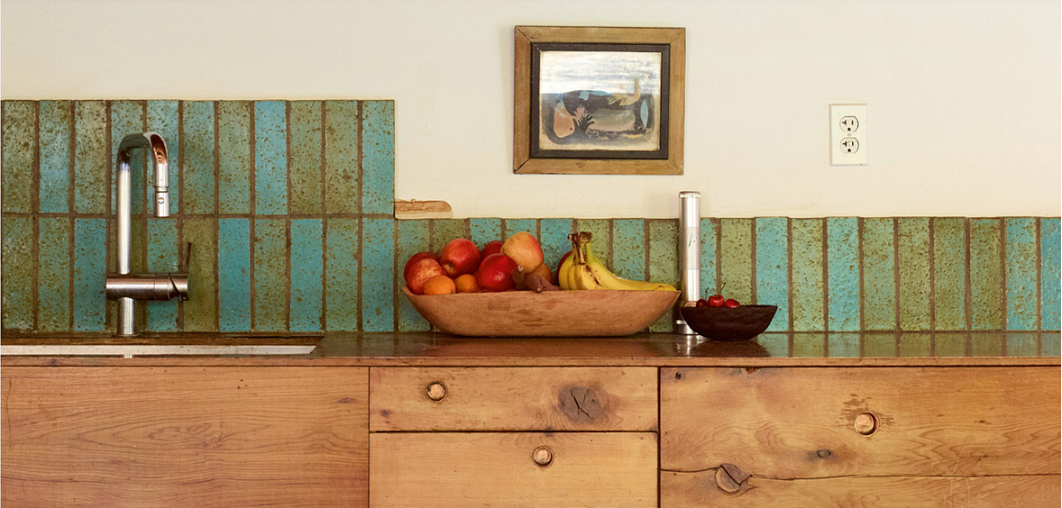 Urban Country kitchen with rustic wood cabinets and blue-green backsplash