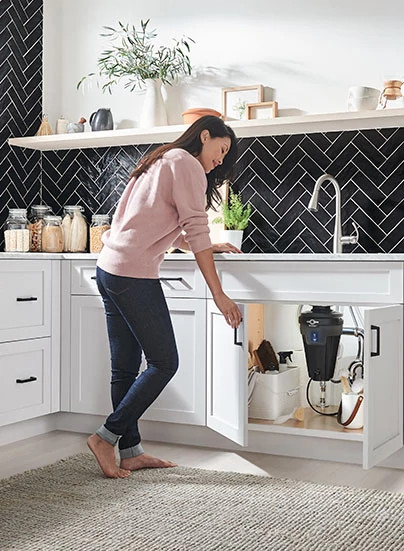 Woman looking under the sink.