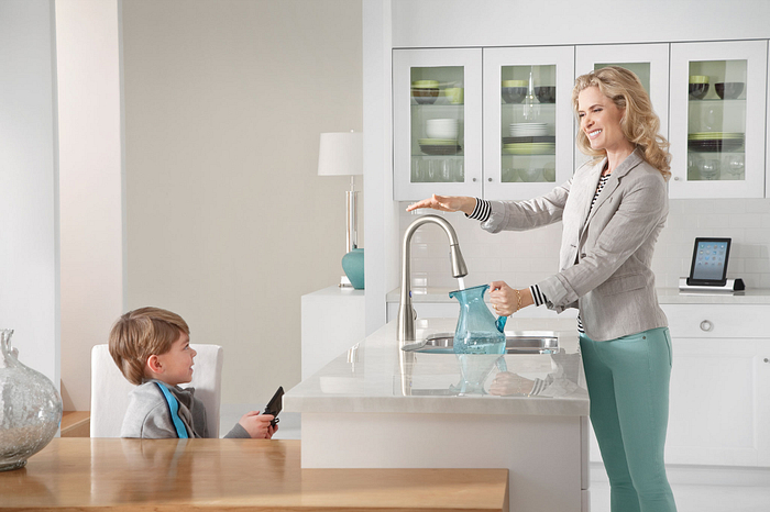 Woman using Moen MotionSense faucet