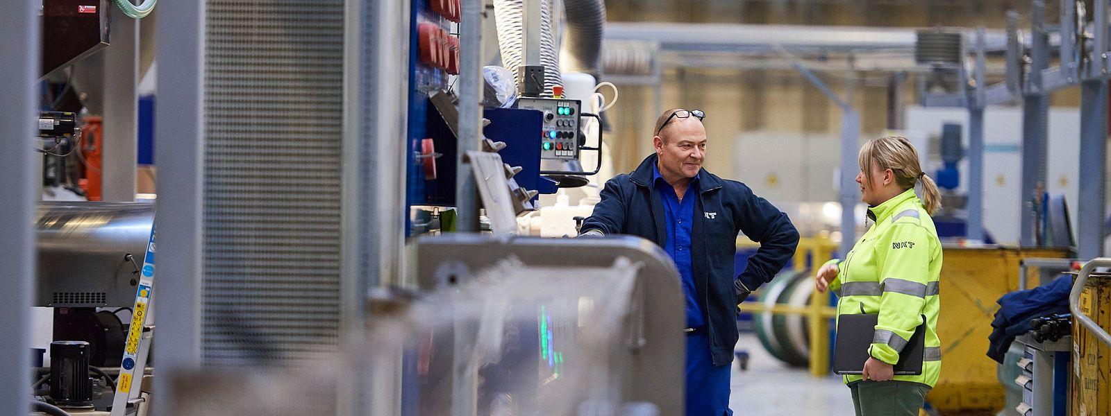 Factory worker talking to office employee