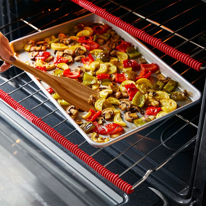 A sheet pan meal baking in an oven with oven rack protectors