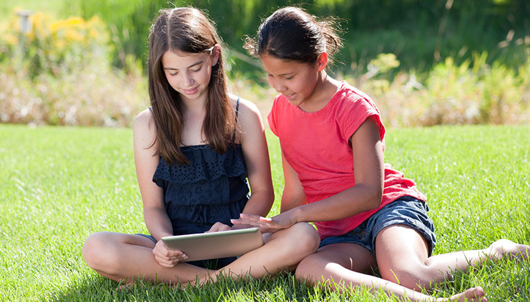 Two girls reading on a tablet in the grass.
