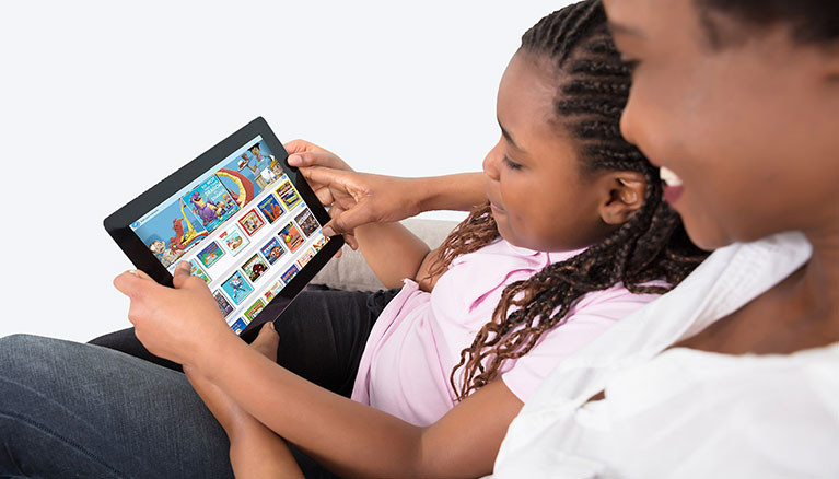 Mother with child looking at a laptop with myON screenshot.