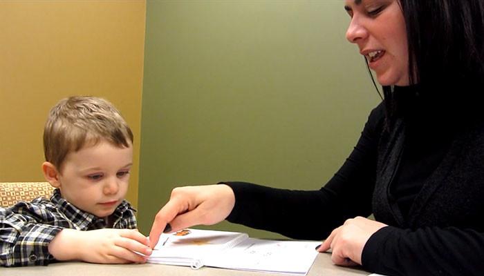 A teacher reading with a little boy.