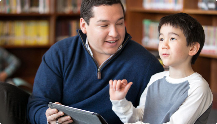 A teacher with a boy and a tablet.