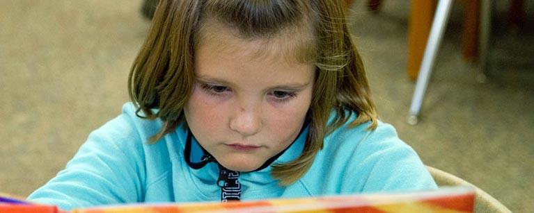 girl-in-class-reading-book-card-767