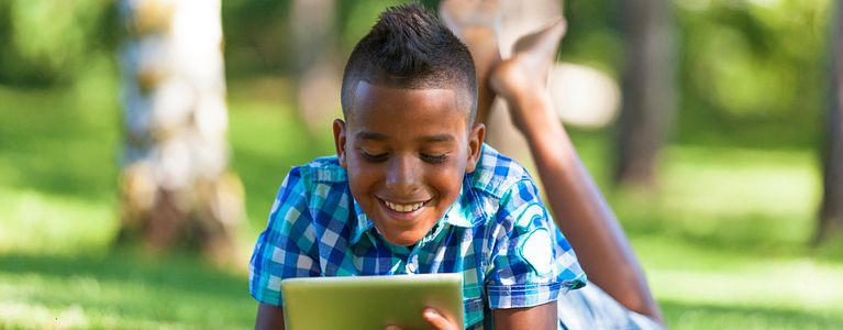 smiling boy reading tablet while laying in grass