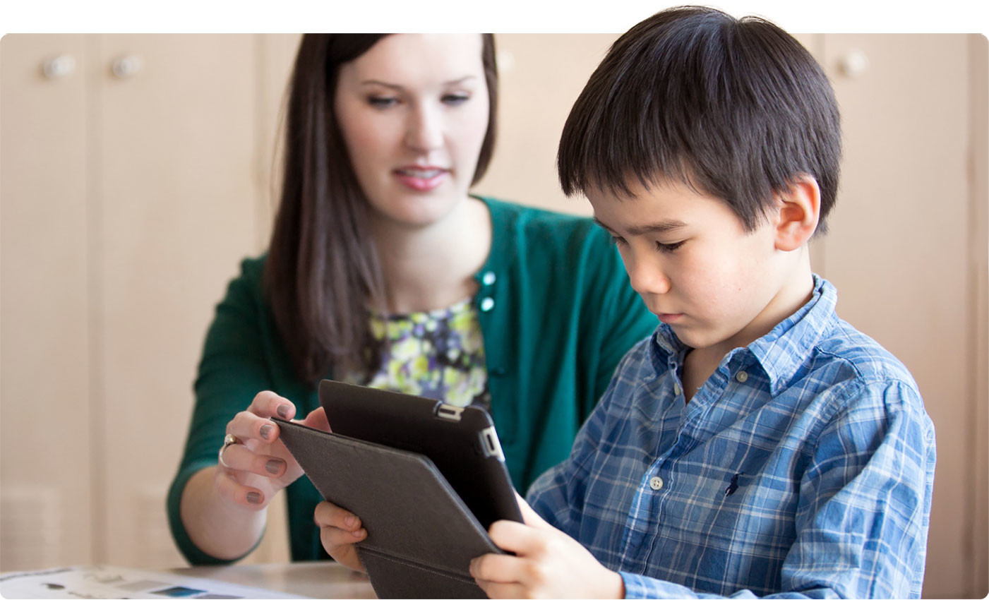 Teacher and young boy with tablet.