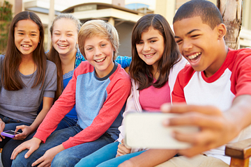 Middle school age children sitting together smiling for a group photo
