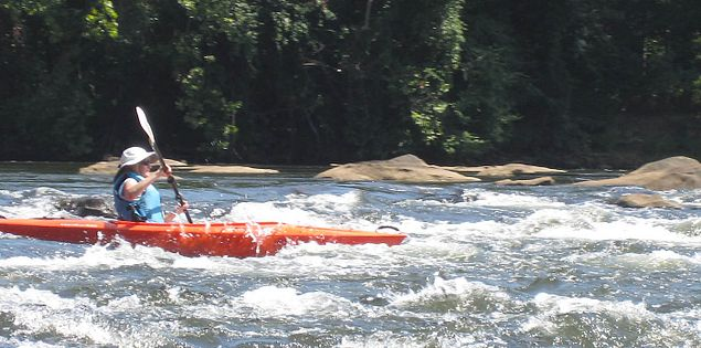 Kayaker navigating on the Catawba River's Class 2 river rapids