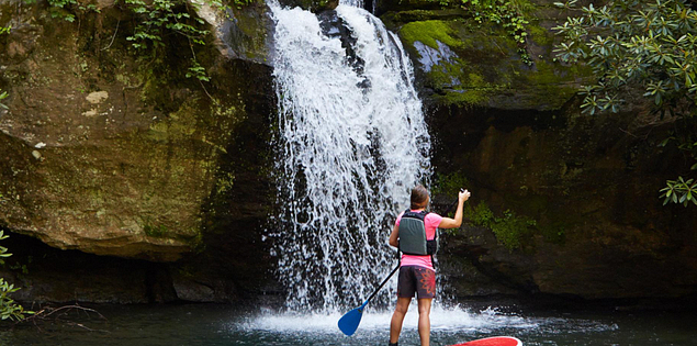 A woman paddleboards in front of Laurel Fork Falls