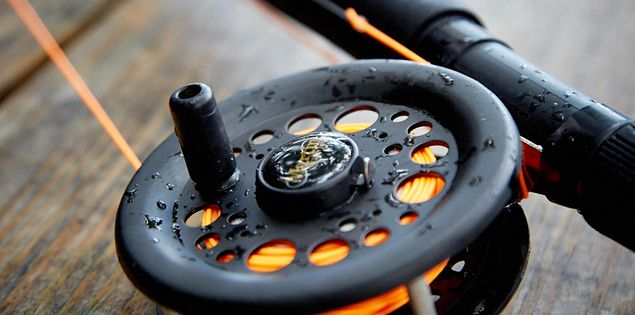A fly reel fishing rods sits on a wooden table