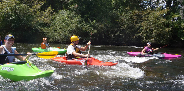 Kayakers paddling through class 1 rapids on the Wateree River
