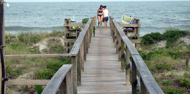 Family walking on boardwalk to Folly Beach on the Carolina Coast
