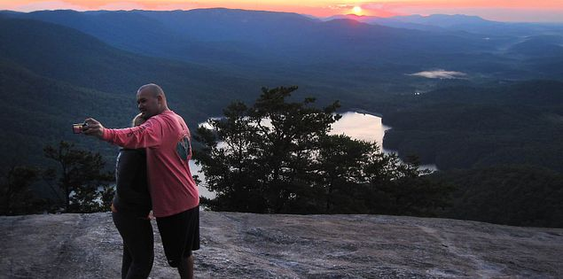 Taking a photo with sunrise on top of Table Rock in Upstate South Carolina