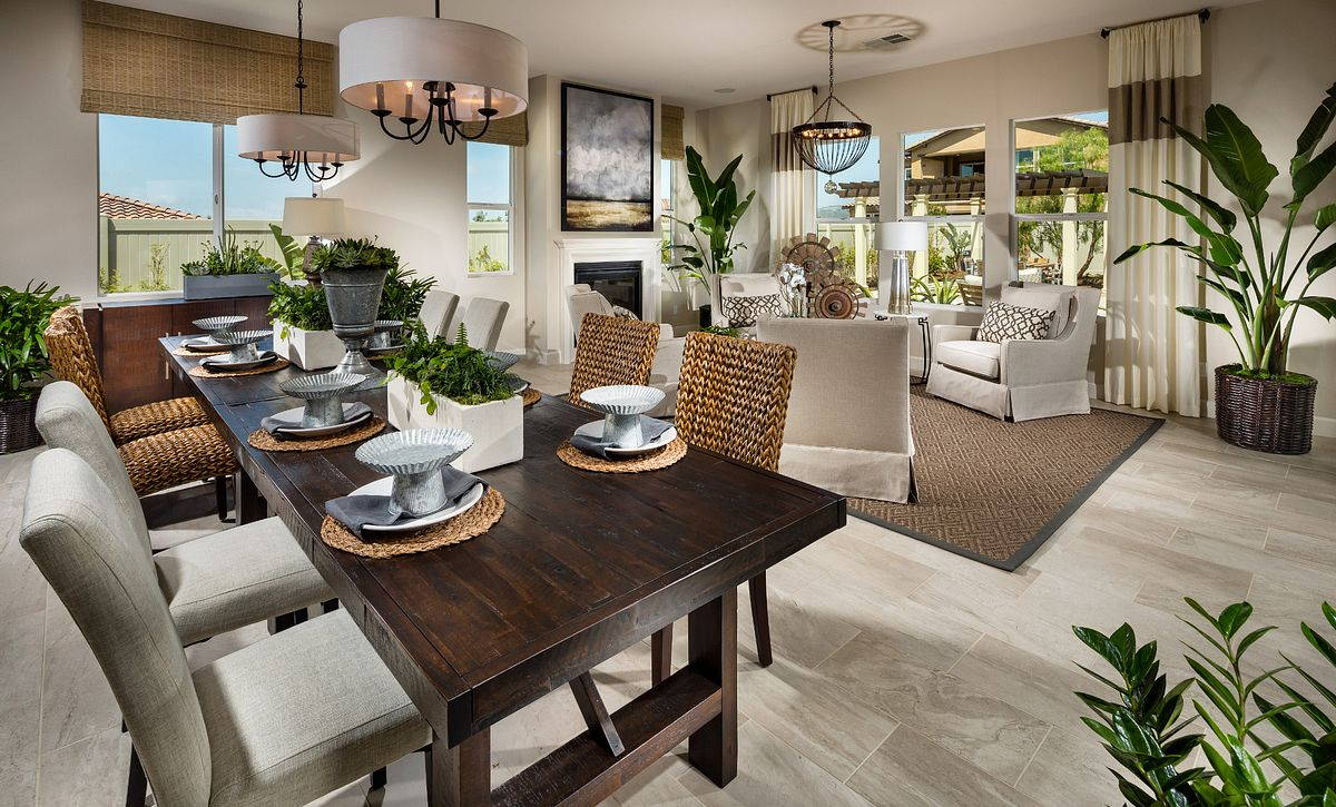 Plan 2 dining room with dining table, surrounding chairs, two chandeliers, and wood floors