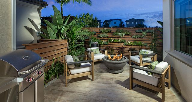 Plan 1 patio with barbecue, firepit, palm tree, and four outdoor club chairs