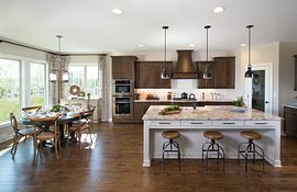 Kitchen with large island, dark cabinets and breakfast area