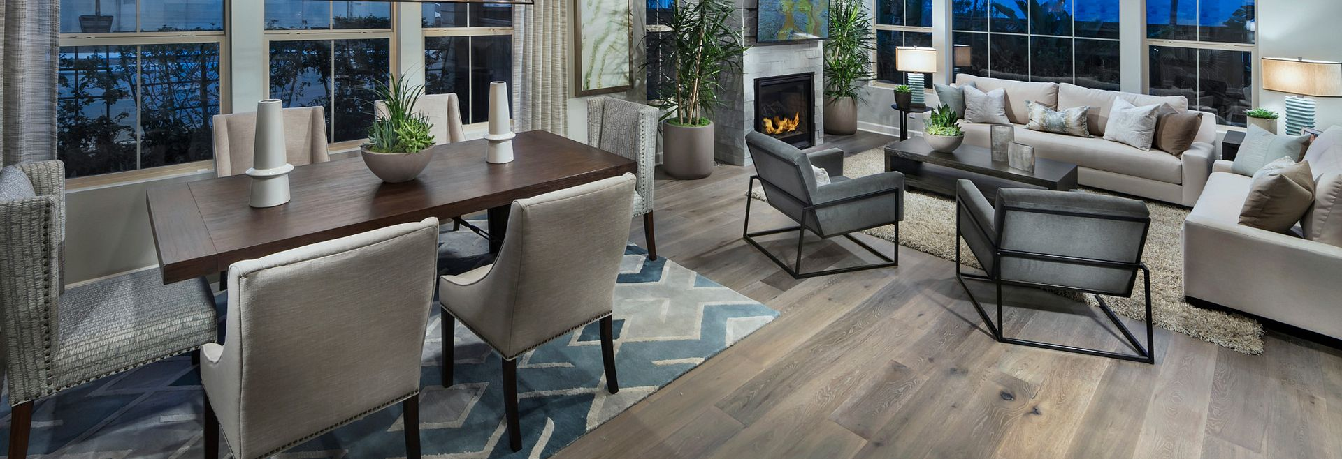 Plan 3 great room with wood floors, dining table, surrounding chairs, area rug, fireplace, sofa, and club chairs