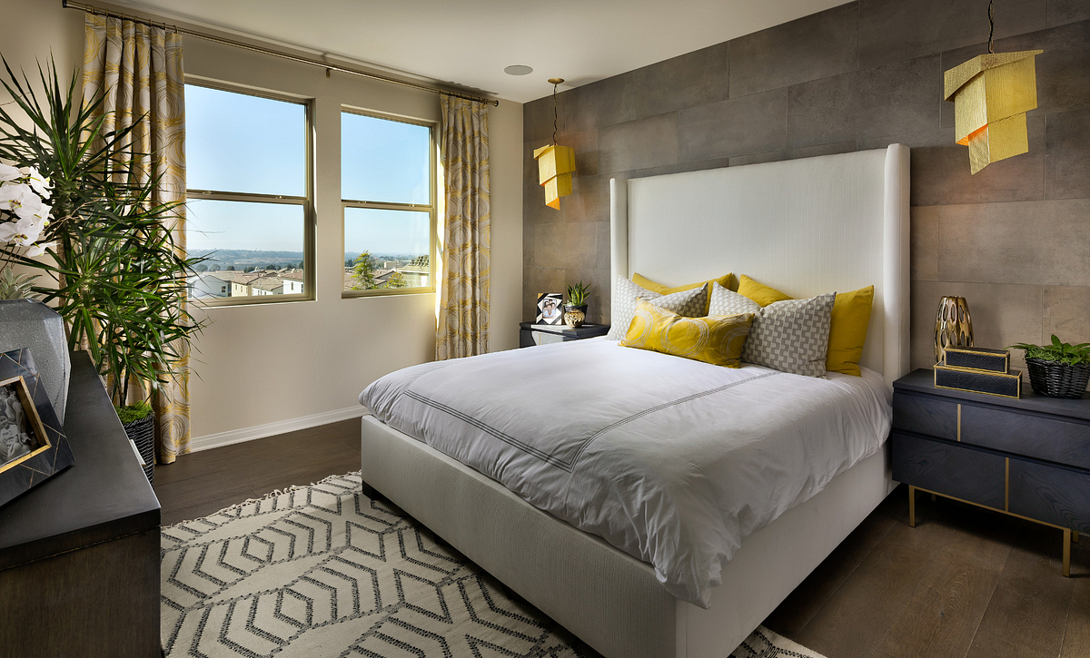 Plan 3 master bedroom with bed, pendant lights, night stands, area rug, wood floors, and dresser