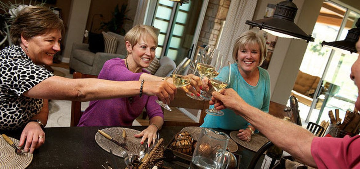 Group of women toasting and clinging wine glasses together