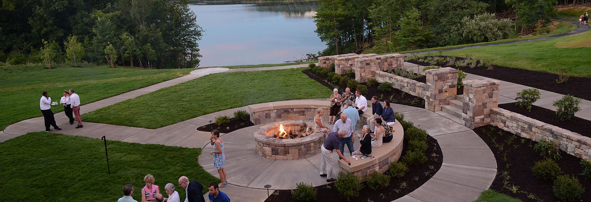 Group of people by the firepit lakeside