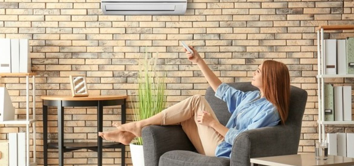 Woman Turning on a Wall Unit Air Conditioner