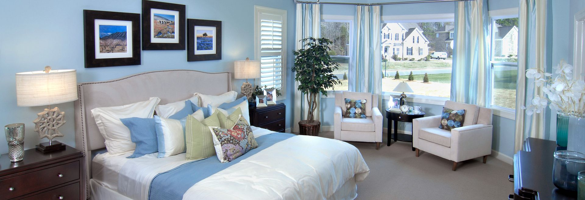 master bedroom with tray ceiling and sitting area