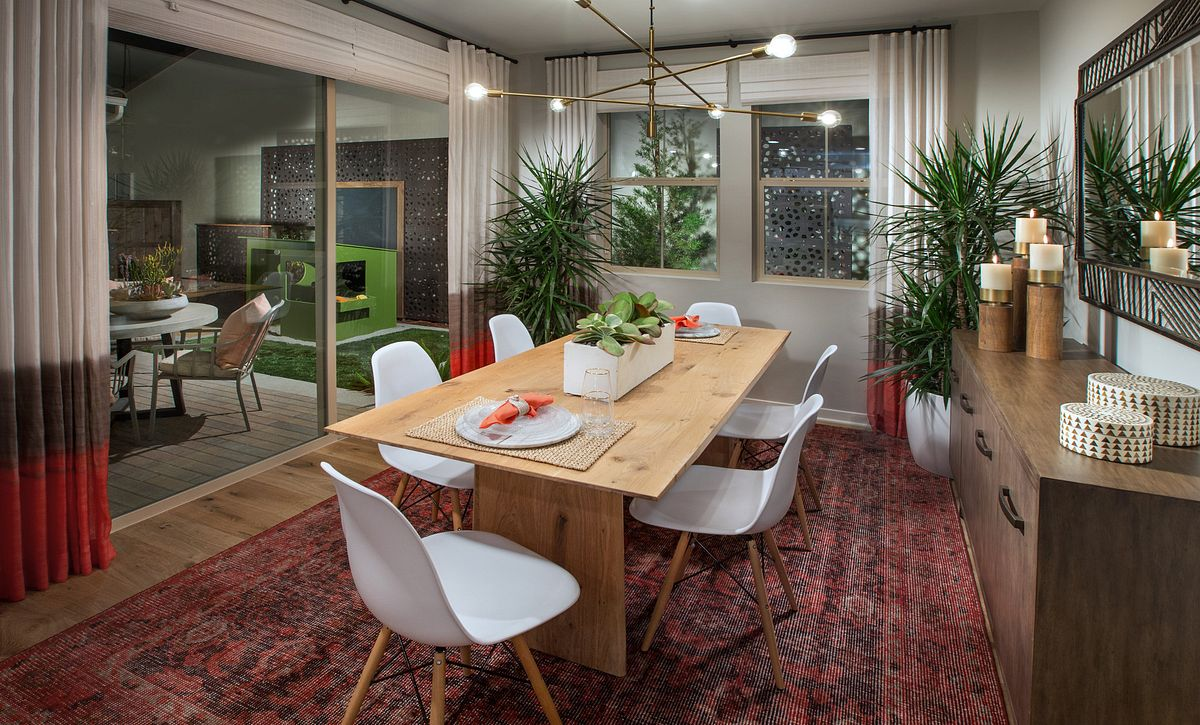 Dining room with wood floors, recessed lights, area rug, dining table, and surrounding chairs