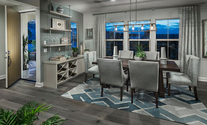 Plan 3 dining room with table, chairs, chandelier, area rug, and windows with drapes