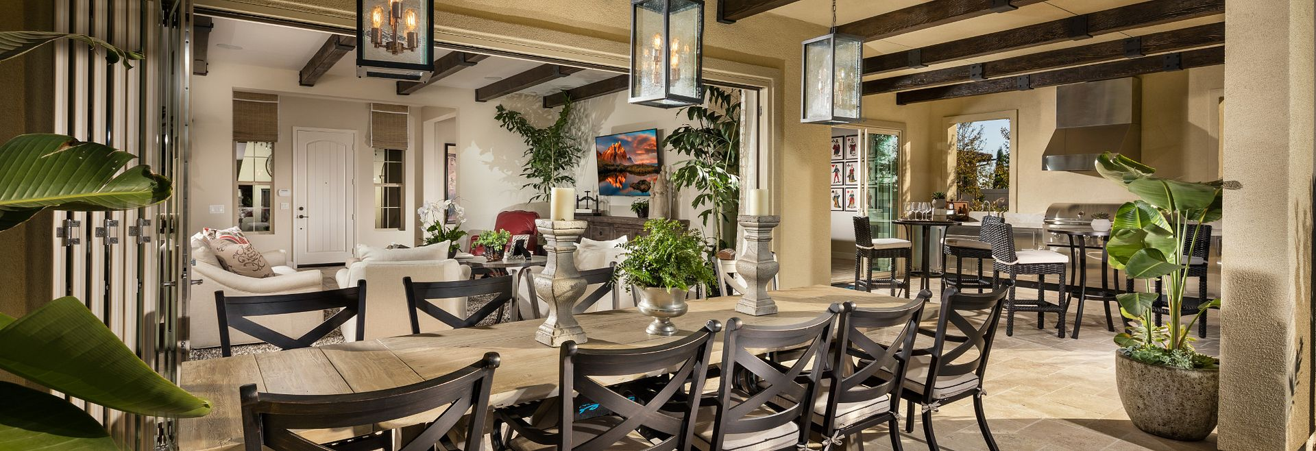 Plan 4 outdoor room with long table, surrounding chairs, and pendant lights