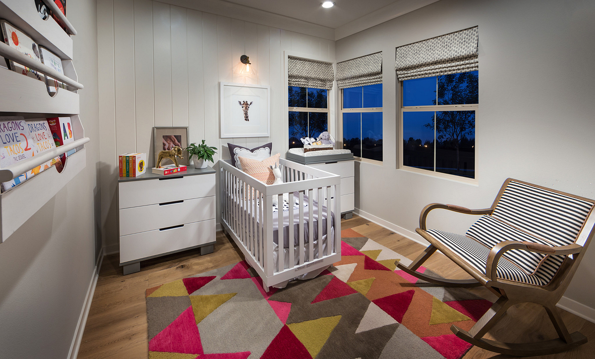 Nursery with white wooden crib, dressing table, rocking chair, three windows and recessed lights