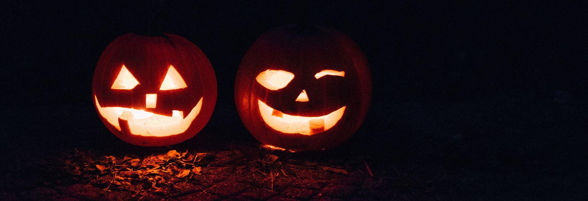 Two Jack-o-Lanterns lit up at night