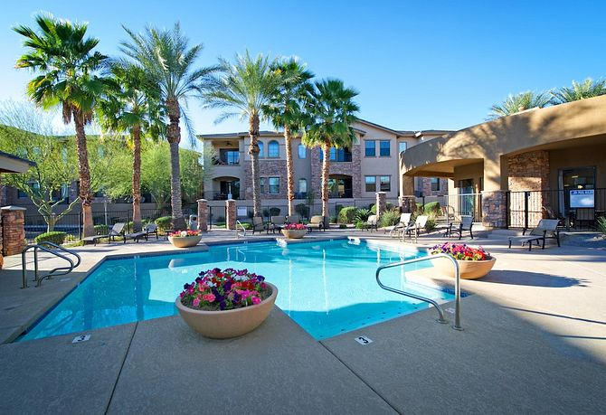 Pool and spa with palm trees and potted flowers