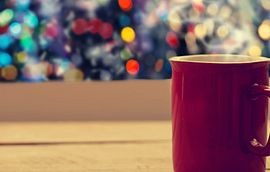 Coffee Mug on table in front of holiday lights
