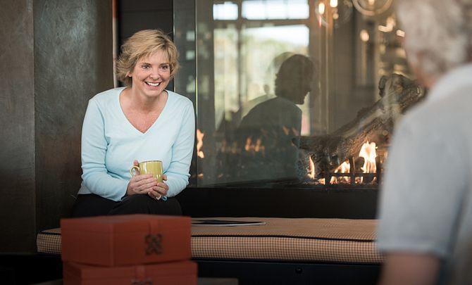 Lady sitting by fireplace with mug