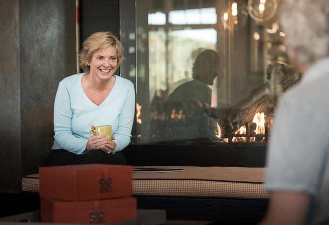 Lady sitting by fireplace with mug
